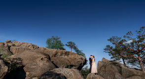 Lonely wedding couple stands on the rocks under deep blue sky.  Royalty Free Stock Photo