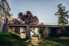 Lonely wedding couple stands under the stone bridge royalty free stock photography
