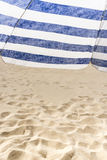 Lonely white and blue strip umbrella on the beach. Close up Stock Photos