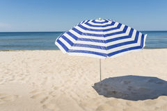 Lonely white and blue strip umbrella on the beach. Close up Stock Photo