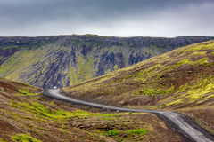 Lonely white car on gravel road in Iceland. HAFNARFJORDUR, ICELAND - AUGUST 26, 2016: Lonely white car is travelling on gravel road through mountains in the stock photos