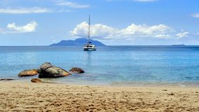 Catamaran boat anchored in a bay in front of the seychelles royalty free stock photo