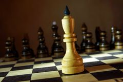 Lonely white chess king in front of enemy team. Unequal fight Royalty Free Stock Image