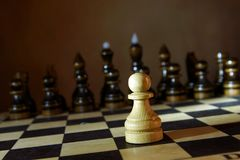 Lonely white chess pawn in front of enemy team. Boldness and courage Stock Photos