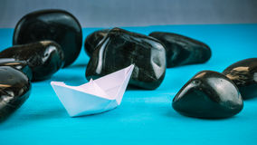 Lonely White Paper Ships between Abstract Black Rock Stones on Blue Background Royalty Free Stock Photo