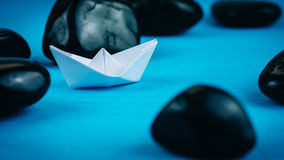 Lonely White Paper Ships between Abstract Black Rock Stones on Blue Background Royalty Free Stock Photography