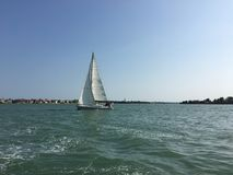 The lonely white sail grows white. A beautiful sailboat in the waters of Venice, Italy Royalty Free Stock Photo