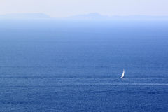 Lonely white sailboat in sea space among blue waves and far horizon. Stock Photography