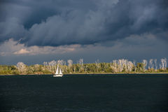 Lonely white sailing boat between dark water and depressing clouds Royalty Free Stock Images