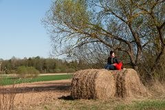 Lonely whomen is siting on the hay. On the background of the countryside near a tree. Solitude. Holding a red heart royalty free stock photography