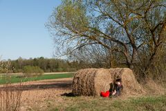 Lonely whomen is siting near a hay. On the background of the countryside near a tree. Solitude. Holding a red heart royalty free stock images