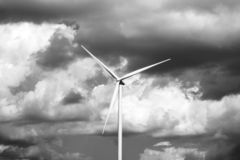 Lonely wind turbine. Stormy sky background. Black and white photography. stock photos