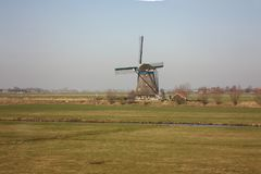 Lonely windmill in the provincial, clean and green countryside of Holland. sky with a bit of mist and pristine green meadows stock photography