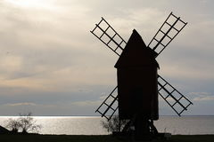 Lonely windmill. A silhouette of an old windmill on the seashore in dull weather stock images