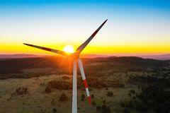 Lonely windmill turbine peacefully rotating blades through the wind in the beautiful sunset sky stock photography