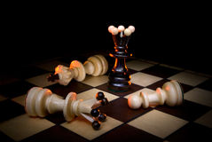 The lonely winner. Black queen and white chessmen. A dark art background Stock Photos