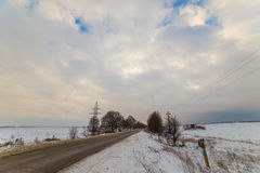 Lonely winter road that goes to the term. around snow. very beautiful clouds at sunset. Royalty Free Stock Images