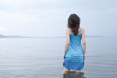 Lonely woman. Stands in water. Blue tones Stock Photography