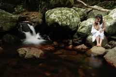 Lonely Woman. A woman sitting beside the stream, queensland, australia Stock Photos