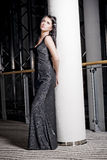 Lonely Woman. A lonely daydreaming woman in a long black glamorous dress, leaning on a pillar Stock Photos