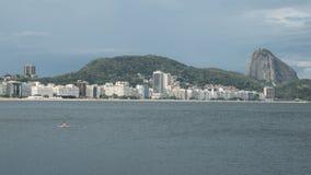 Lonely woman adrift overlooking Copacabana Beach, Rio de Janeiro. Lonely woman adrift on a paddleboat overlooking iconic Copacabana Beach in Rio de Janeiro Royalty Free Stock Photography