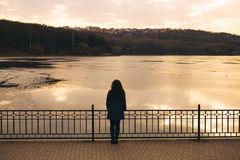 Lonely woman alone in winter at sunset. Lonely woman watching sunset alone in winter at sunset. Sad abstract concept of girl silhouette in love Stock Photos