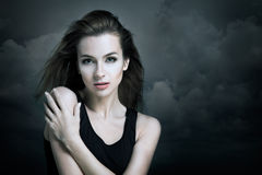 Lonely Woman on the Background of Dark Clouds Stock Photo