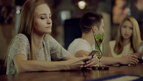 Lonely woman in a bar. Young upset lonely woman sitting in a bar using a phone with happy couple on background stock video footage