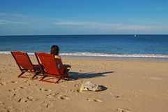 Lonely woman on the beach. Lonely woman and two deck chairs on the beach royalty free stock photography