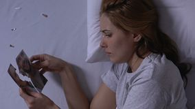 Lonely woman in bed holding pieces of torn photo and crying, husband betrayal. Stock footage stock video