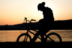 Lonely woman on bicycle by sea