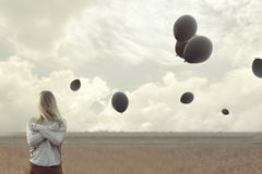 Lonely woman with blacks balloons hid her face. In a surreal place Stock Images