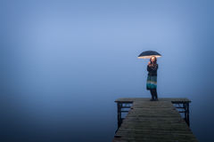 Lonely woman on bridge with umbrella Stock Photos