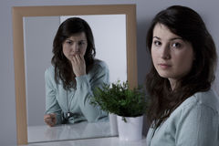 Lonely woman with complexes. Looking at the mirror Stock Image