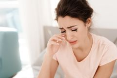 A lonely woman is crying alone, her mascara has flowed. She sits on a bed in a bright room. Royalty Free Stock Images