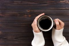 Lonely woman drinking coffee in the morning, top view of female hands holding cup of hot beverage on wooden desk Royalty Free Stock Photography