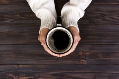 Lonely woman drinking coffee in the morning, top view of female hands holding cup of hot beverage on wooden desk Royalty Free Stock Photos