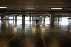 Lonely woman in the empty shopping mall parking lot. Dark Royalty Free Stock Image