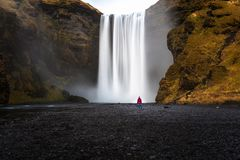 Lonely Woman at the Foot of an Impressive Waterfall royalty free stock images