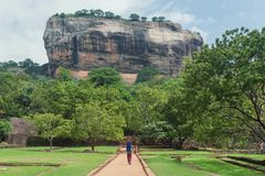 Lonely woman in headscarf walking to famous landmark Sigiriya rock, Sri Lanka. UNESCO world heritage site Royalty Free Stock Image