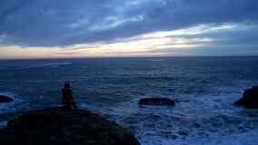 lonely woman in jacket sitting at the wavy sea with dramatic sky, loneliness