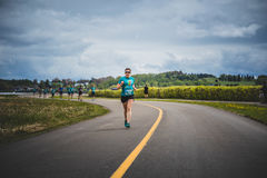 Lonely Woman Leading a Group of 10K Runners Stock Photo