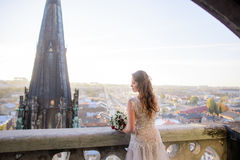 Lonely woman with long curls bends over the balcony Royalty Free Stock Photography