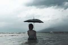 Lonely woman meditating looking at infinity in the rain and thunderstorm Royalty Free Stock Images