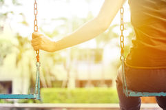 Lonely woman missing her boyfriend while swinging in the park villa in the morning Royalty Free Stock Photography