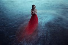 Lonely woman near the sea. Lonely woman in red dress near the sea Stock Photography