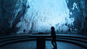 Lonely woman praying in the Salt Cathedral of Zipaquira is an underground Roman Catholic church built within the tunnels of a salt royalty free stock images