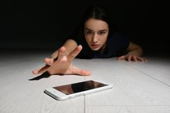 Lonely woman reaching out for smart phone on floor indoors stock images
