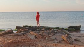 Lonely woman in the red t-shirt is standing on stones at the shore She waiting for sunrise
