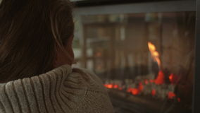 Lonely woman resting near fire place, rear view. stock video footage